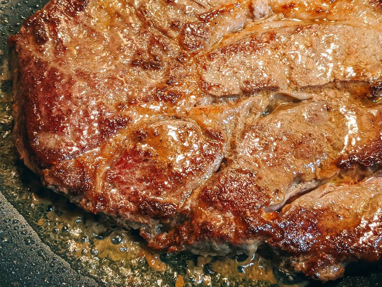 ステーキ肉をフライパンに入れて焼いている画像アップ