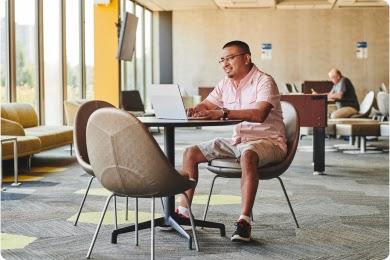 Hombre con gafas, camisa rosa de botones y pantalones cortos sentado frente a su computadora en una mesa de un espacio de trabajo.