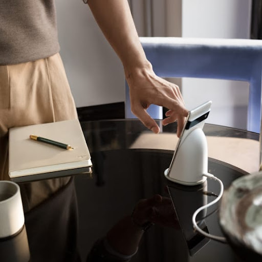 A person touches the Pixel's display as it sits upright and charges on a desk.