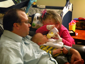 Photo: Ella giving AJ his first bottle. He took it like a champ!