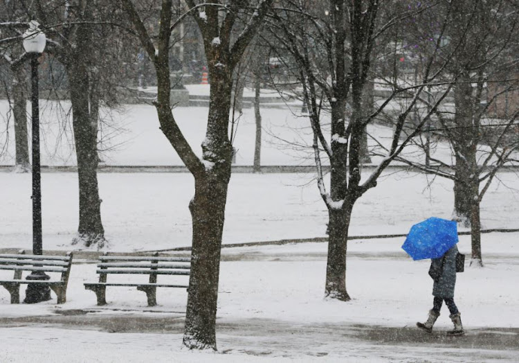A pedestrian walks through Boston Common during a winter snow storm in Boston, Massachusetts, US, January 17, 2018.