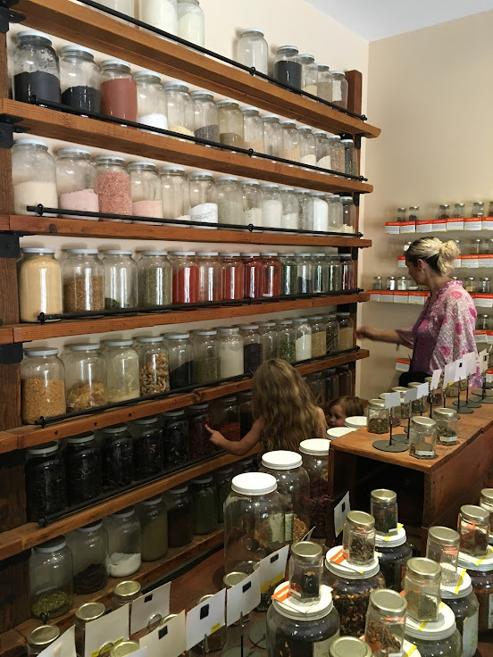 Giant glass jars of spices line the walls.