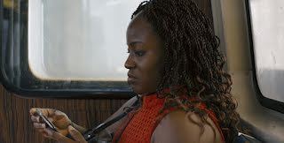 close up of side of woman's face as she looks at her phone