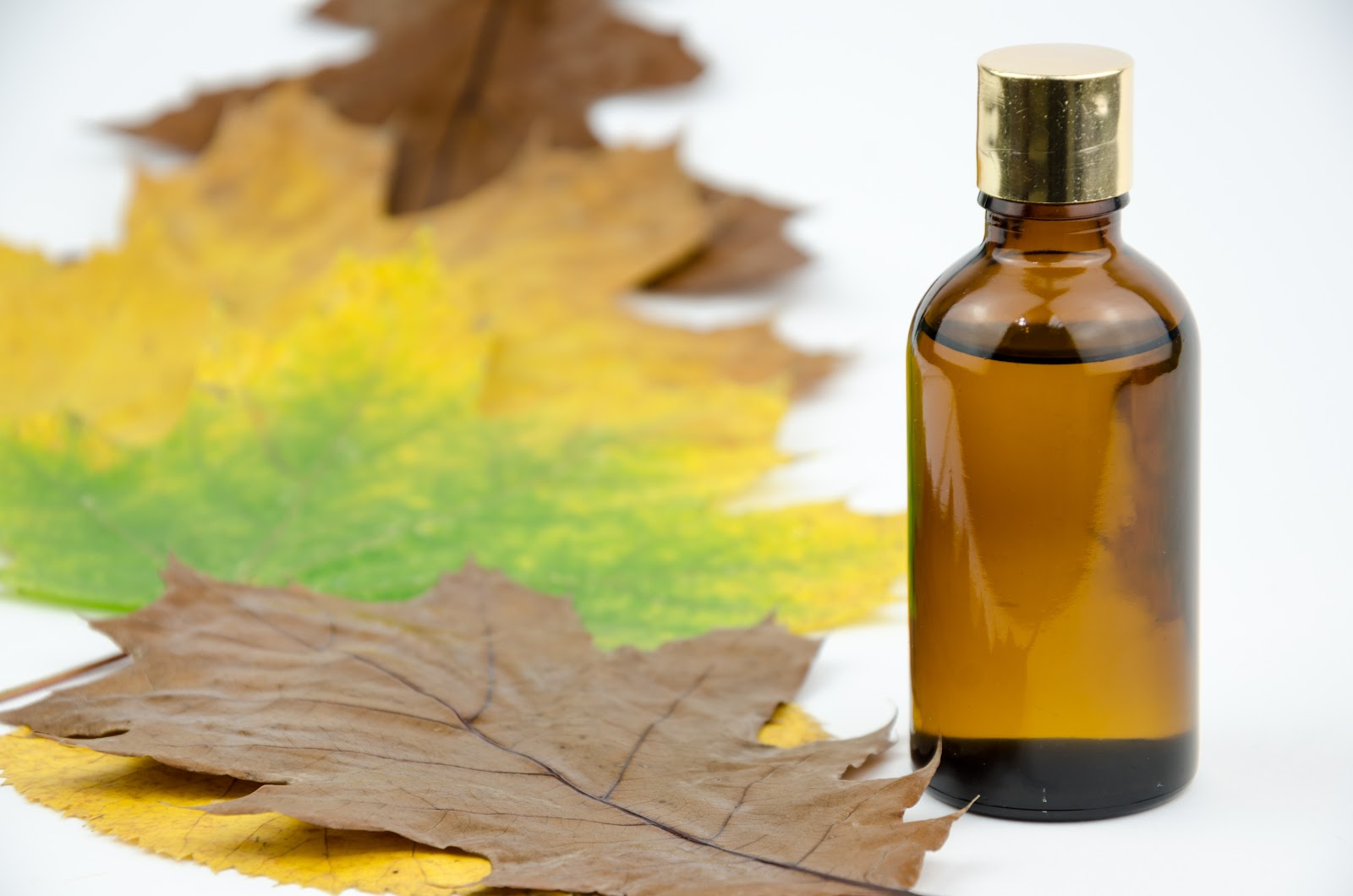 fall leaves next to a perfume bottle