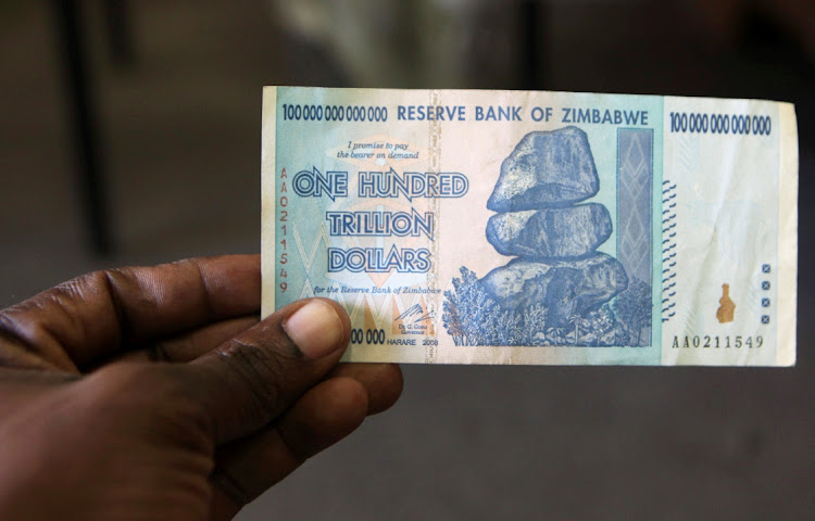 A man holds up for a picture a one hundred trillion Zimbabwean dollars note inside a shop in Harare, Zimbawe in June 2015. Picture: REUTERS/ PHILIMON BULAWAYO
