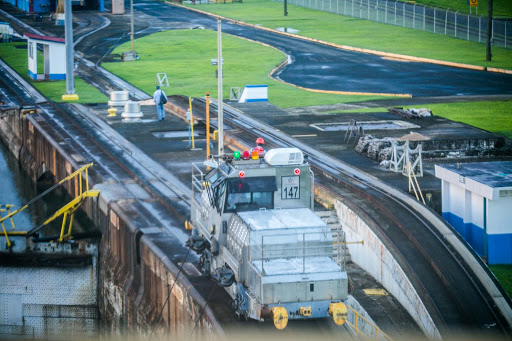 "panama-canal-mule-in-action2.jpg - Electric locomotives, called ""mules,"" guide a ship through a Panama Canal lock."