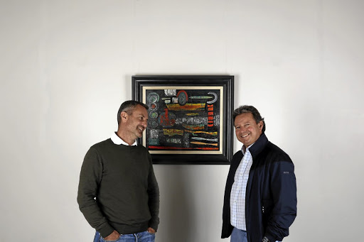 Frames of reference: Frank Kilbourn, left, and fellow abstract art collector Pieter Colyn stop to admire a work by SA artist Walter Battiss in 2017. Picture: SUPPLIED