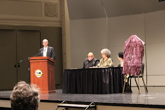 Photo: Chancellor Lovell at the podium. Special Guest Speaker Dr. Maulana Karenga, his wife and Dr.Kirk on stage.