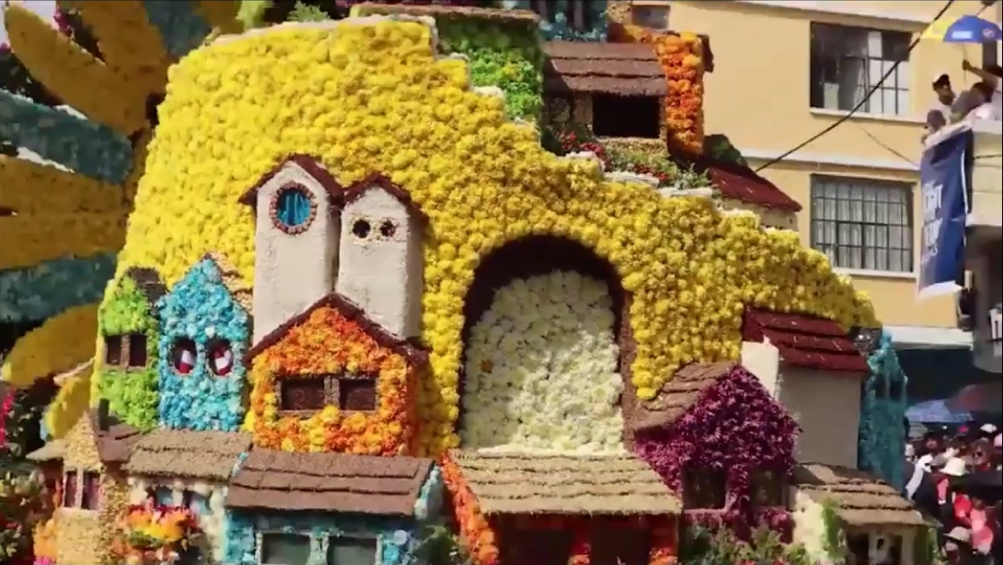 Flower-covered float depicting houses and buildings from a traditional neighborhood of Ambato. During Fruits and Flowers Festival.