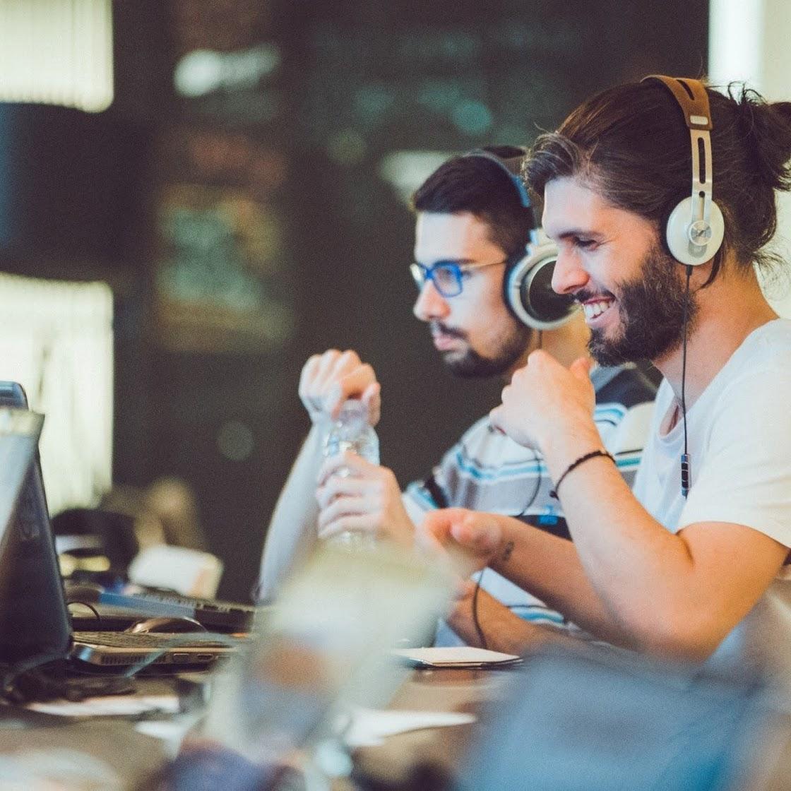 Team member watching a video on laptop while wearing headphones