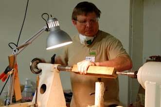 Photo: Here, Mike shows a quick trick -- how to drill a hole in a spindle for making a tool handle. Note that the drill bit is in the headstock, not the tailstock. He brings the tool rest up to stop the blank from spinning, and the hole is created instantly by cranking in the tailstock quill.