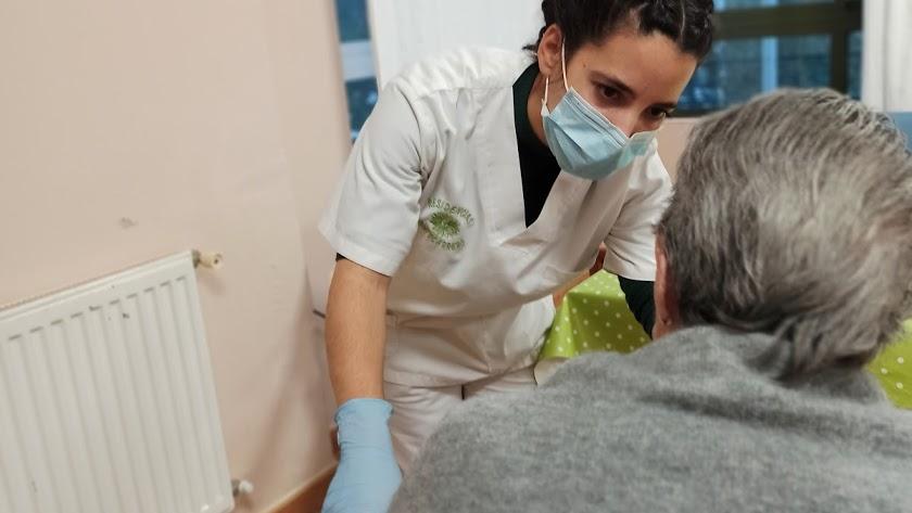 Una residente en un geriátrico atendida por una profesional con mascarilla.