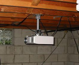 Photo: The AX100U hanging from the ceiling. This will also change when construction starts as the projector will set on a shelf  shine through an opening in the back wall.