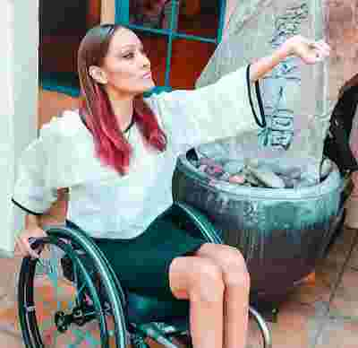 A photo of Angela Rockwood, a glamorous young woman with dyed red hair, sitting in a wheelchair holding her wrist out.