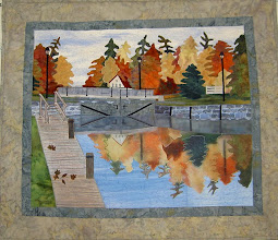 "Photo: Chaffey's Locks.This wall hanging was made for a challenge by the International Plowing Match in Ontario, 2008. The theme was ""On the Rideau"" and this landscape was designed from a photograph of the locks.The reflection in the water was made by copying the trees on the computer, mirror image, fading out and copying on fabric."