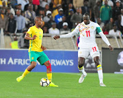 England-based SA midfielder Kamohelo Mokotjo protects the ball under the guard of Cheikh Ndoye during the 2018 FIFA World Cu qualifier match between Bafana Bafana and Senegal at Peter Mokaba Stadium in Polokwane on November 10, 2017.