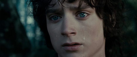 Elijah Wood in The Lord of the Rings. A close-up of Frodo as he gazes intently off-camera with his brow creased, tears rolling down his cheeks. His eyes are bright blue against the forest backdrop.
