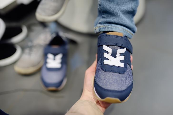 子どもに靴を履かせる親の手