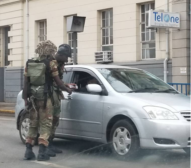Member of Zimbabwe's elite parabat squad, or special forces, check identity particulars of civilians in Harare. Picture: SUPPLED
