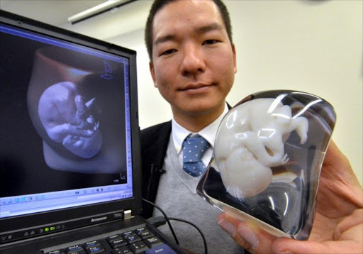 This photo taken on November 26, 2012 shows Japan's 3D computer-aided design (CAD) venture Fasotec employee Tomohiro Kinoshita displaying a nine-month fetus and mother's body image, made of two-colour acrylic resin at the company's headquarters in Chiba, suburban Tokyo.