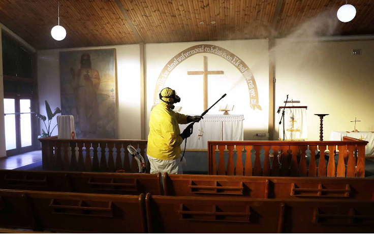 A man sprays disinfectant as he sanitises the Evangelical Lutheran Church in Belgravia, Athlone, to prevent the spread of Covid-19 in Cape Town.