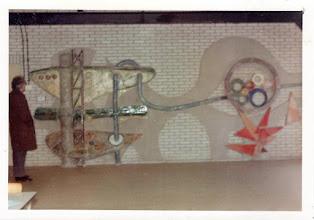 Photo: 1972 ca. Monumentaal reliëf in de kantine van verwarmingsbedrijf Onnekink, aangeboden door het personeel, lengte 4 meter, beschrijving manshoog, afgebeeld techniek, geometrie, slang, veelkleurig, links geeft de kunstenaar tevens het formaat aan. Gedateerd 1970-1975 wat betreft haarkleur en kwaliteit foto