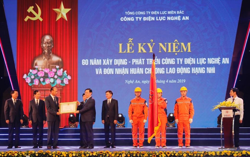 Đồng chí Vương Đình Huệ - Phó Thủ tướng Chính phủ gắn Huân chương Lao động hạng Nhì lên lá cờ truyền thống và trao Huân chương Lao động hạng Nhì cho Điện lực Nghệ An