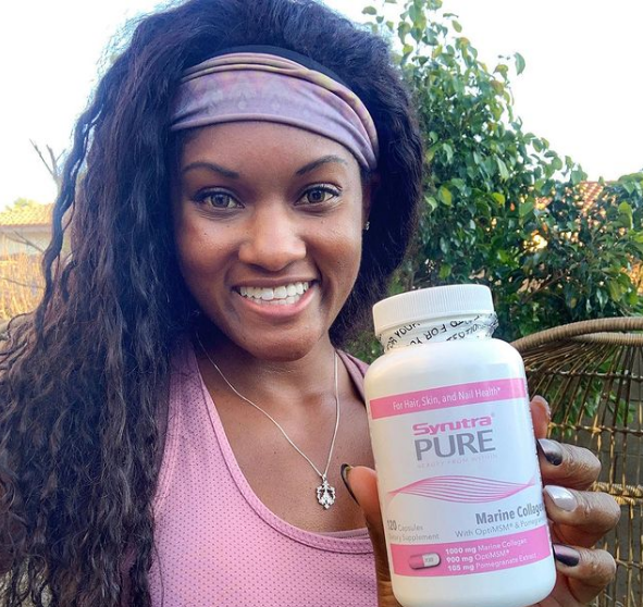 Brittany Noelle promoting a bottle of Synutra Pure | Black Influencers Featured on Afluencer
