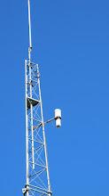 """Photo: En déport, la balise 10 GHz, partie multiplication par 96 et PA 2W, antenne à fentes. Notez le """"radôme"""" qui est aujourd'hui un gros tube de PVC et son chapeau..."""