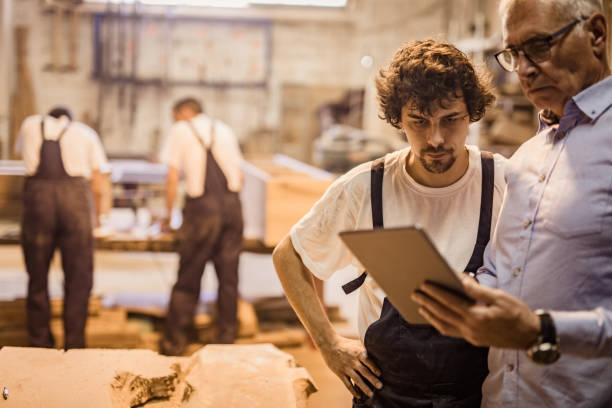 two man reading a plan for a woodworking workshop