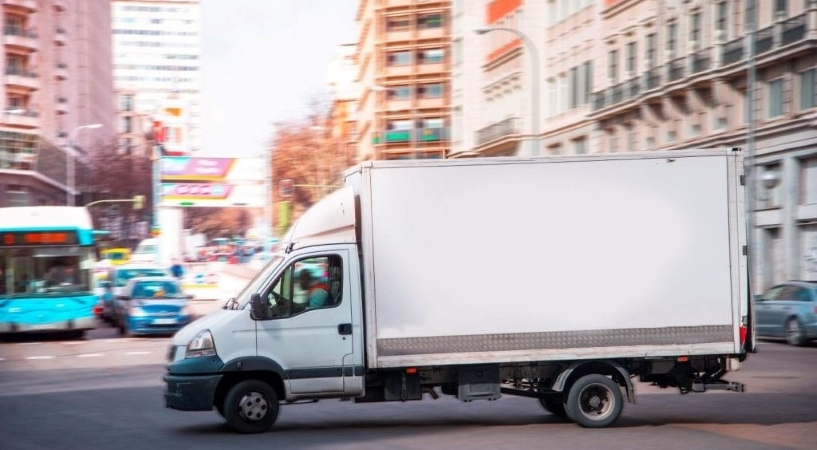 a moving truck navigates its way through a big city