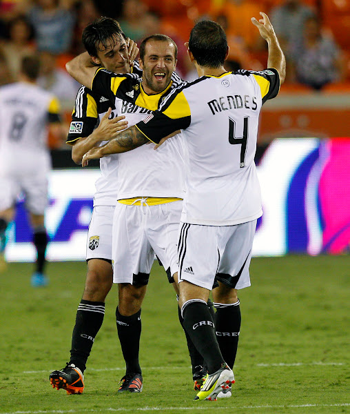 Photo: HOUSTON, TX - AUGUST 19: Federico Higuain #33 celebrates with Cole Grossman #22 of the Columbus Crew and Carlos Mendes #4 of the Columbus Crew after Eddie Gaven #12 of the Columbus Crew scored against the Houston Dynamo at BBVA Compass Stadium on August 19, 2012 in Houston, Texas.  (Photo by Bob Levey/Getty Images)