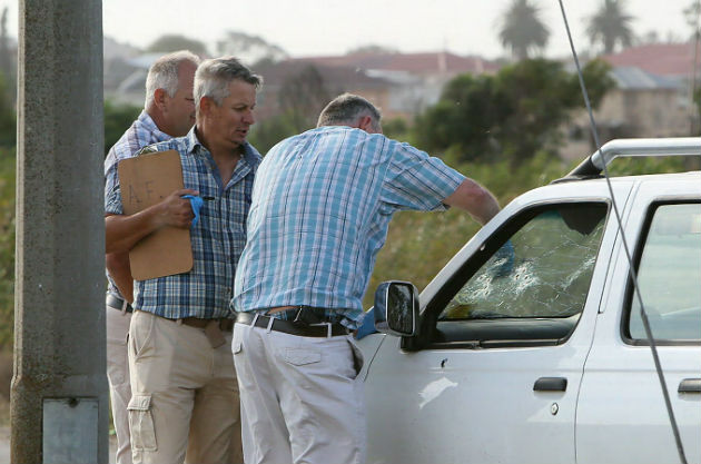 Officers gather evidence from the bullet-ridden windscreen of a bakkie caught in the crossfire