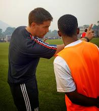 Photo: Coach McKinstry provides half time advice to Santigie Koroma (CBF) before his debut for Sierra Leone U20 [versus Guinea in 2015 CAF U-20 first round qualifying (Picture: Myrthe van Vliet)]