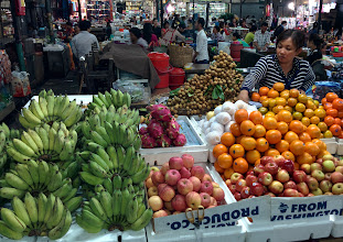 Photo: A fruit stand in the Old Market. The fruit at lower left are short bananas, not plantains (I believe). Next to the vendor is a pile of lychee (or longan?) still in their tough brown skins. Nexus 5/HDR+