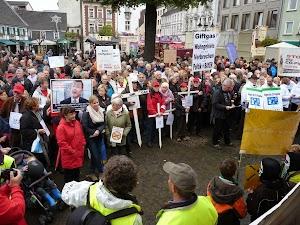 Menschenmenge mit Protestplakaten und Kreuzen.