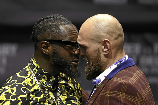 Professional boxers Deontay Wilder, left, and Tyson Fury butt heads onstage during a press conference to promote their upcoming fight. /Victor Decolongon/Getty Images