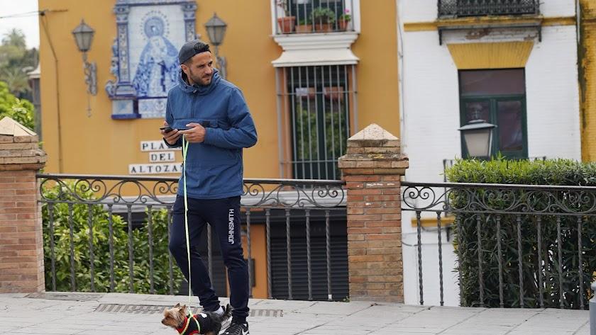 Un joven pasea a su perro en el barrio sevillano de Triana.
