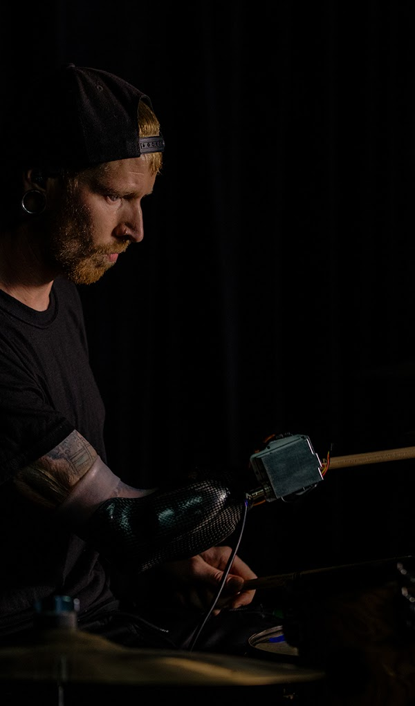 Jason Barnes playing the drums on a stage lit by blue stage lights.