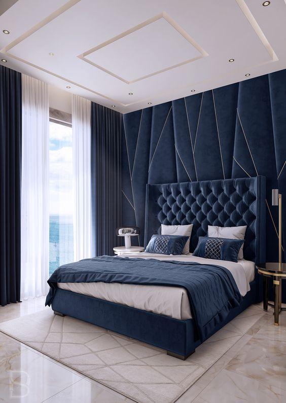 Quarto de casal com cabeceira estofada azul e parede de fundo com papel de parede geométrico azul com detalhes brancos, piso porcelanato imitando pedras e tapete claro.