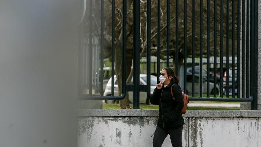 Una mujer pasea con mascarilla por una vía pública.