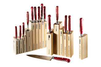 """Photo: BERTI """"Insieme"""" collection of 24 individual knives with red Lucite handles and magnetized wooden blocks. $300–$510. Also available in ox horn. Italy. Seventh Floor. 212 872 2686"""