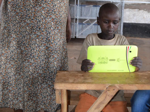 Standard 1 pupil Nicholas Kyete holds a tablet at Muthue Primary School in Kitui South subounty as a tacher looks on.