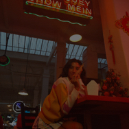 Woman eating Chinese food at a restaurant countertop