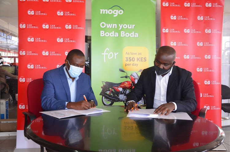 Car & General GM consumer products George Rubiri (left) with Mogo Auto Kenya relationship manager Aloise Ngari during the signing/