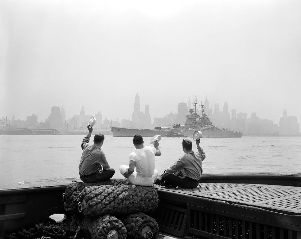 Three sailors wave their hats at the Jean Bart, a French Battleship, as it sails past New York City