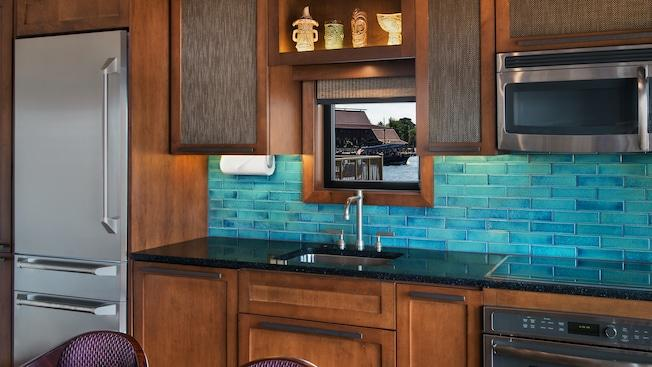 A modern kitchen with a refrigerator, sink, stove, microwave and winow overlooking Seven Seas Lagoon