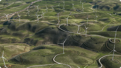 Green rolling hills dotted with wind turbines