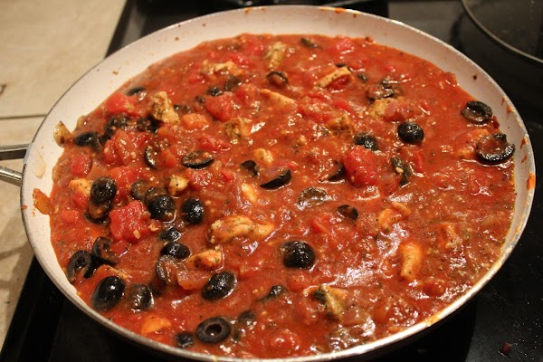 Once the chicken is fully cooked add the jar of tomato sauce, the undrained...