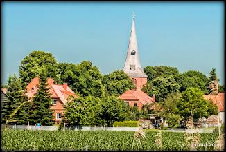 Photo: Der Bau der St. Marienkirche in Stapel an der Elbe wurde im Jahre 1291 vollendet. Sie ist die älteste und größte Kirche im heutigen Amt Neuhaus. Lange Zeit war sie dort die Hauptkirche; der erste lutherische Prediger ist hier 1543 aktenkundig. Der Turm ist wahrscheinlich der älteste Teil der Kirche. Seine Mauern sind bis zu zwei Meter dick, den Turmhelm, der in der Form einer Mütze ähnelt, decken 23000 Eichenholzschindeln. Vom 37 Meter hohen Turm aus hat man einen phantastischen Blick in die Elbmarsch. Nach wie vor werden die Zeiger der Turmuhr von einem mechanischen Uhrwerk aus dem Jahre 1873 bewegt. Die älteste der drei Glocken stammt von 1408.  Die größte bauliche Veränderung der Kirche erfolgte zwischen 1851 und 1855. Der Dachstuhl des Kirchenschiffs wurde erneuert. Die Fenster wurden neugotisch verändert. Der gesamte Innenraum erhielt eine neue Gestalt. Der reich verzierte barocke Altar kam aus dem Ostchor an die Südseite der Kirche.